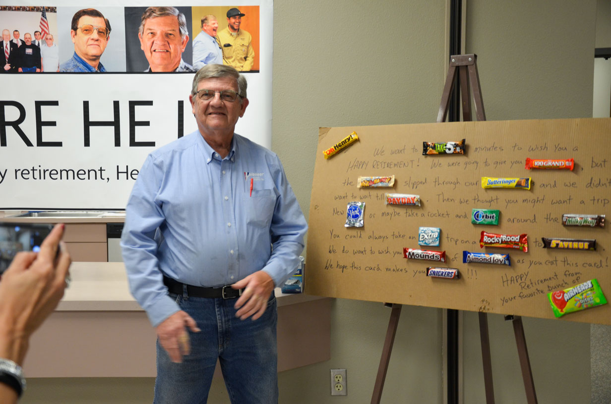 Henry Stands next to a retirement card from his employees.